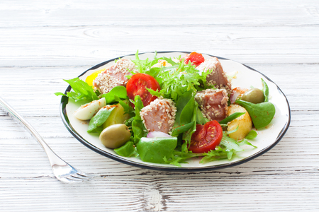 Vegetable salad with grilled tuna ( Nicoise), lettuce, tomatoes and olives  in white plate over white wood background
