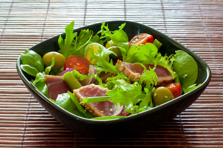 Vegetable salad with grilled tuna ( Nicoise), lettuce, tomatoes and olives  in black plate