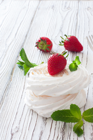 Meringues with fresh strawberries and mint on white wood background. Close up Stock Photo
