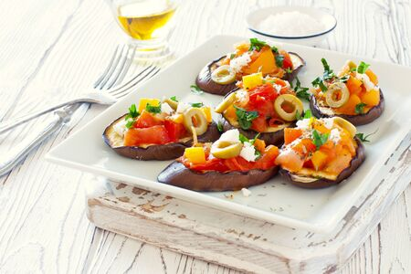 Grilled Eggplants, Tomatoes, Peppers and Green Olives Snack Served on a White Plate on White Wood