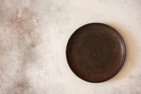 Empty clay  plate on stone  background. Top view with copy space