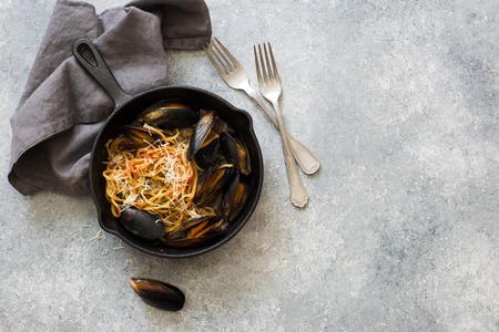 Spaghetti  with mussels and spinach in black bowl on a grey stone background. Flat lay. Copy space Imagens