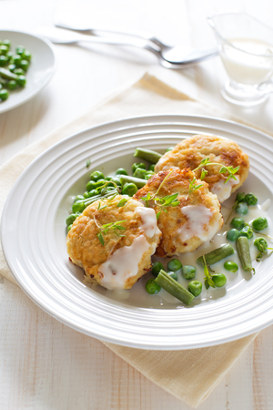 Fish cutlets with green peas and beans on a white plate on white wooden background close up