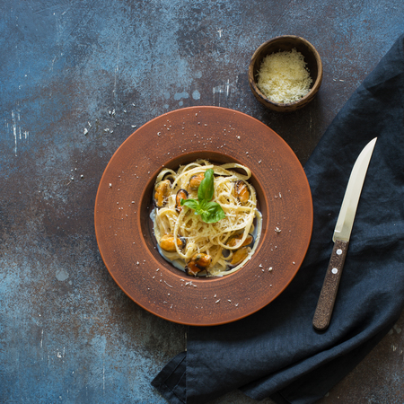 Italian pasta with mussels and parmesan on a grunge stone background. Flat lay
