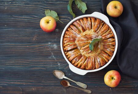 Baked whole apple pie on a dark wooden background. Flat lay. Copy space