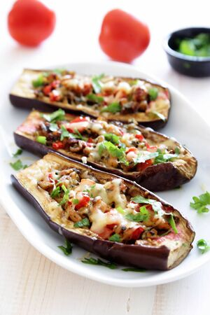 Eggplants stuffed with meat, mushrooms and tomatoes close up. Selective focus
