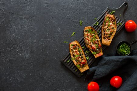 Eggplants stuffed with meat, mushrooms and tomatoes served on a black ceramic plateon a stone background. Flat lay. Copy space