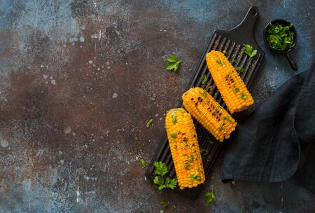 Grilled sweet corn with spices served on a black ceramic plate on a grunge stone background. Flat lay.Copy space