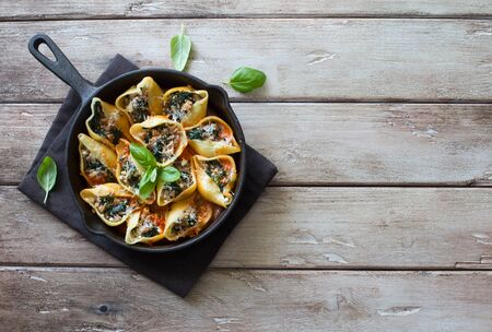 Conchhhiglioni stuffed with meat and spinach served in a skillet on a natural wooden background. Flat lay. Copy space