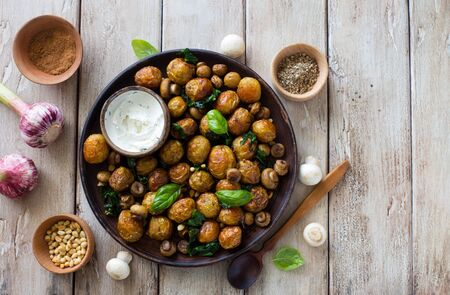 Fried little potatoes and mushrooms on clay  plate on natural wooden background. Flat lay. Copy space Banque d'images