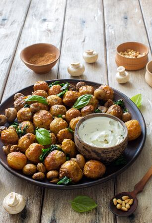 Fried little potatoes and mushrooms on clay plate on natural wooden background close up