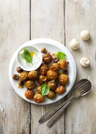 Fried little potatoes and mushrooms on white plate on natural wooden background. Flat lay. Copy space