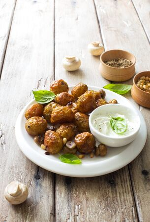 Fried little potatoes and mushrooms on white plate on natural wooden background close up