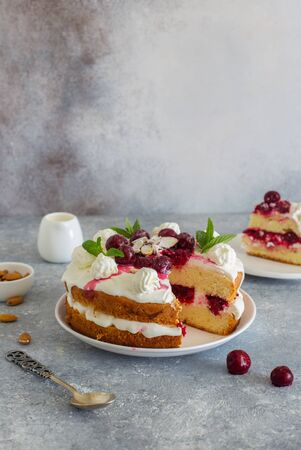 Delicious tart wih cherries, almond flakes  and whipped cream close up on gray stone background Banque d'images