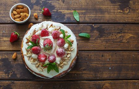 Delicious tart wih fresh strawberries and whipped cream on natural wooden background. Flat lay. Copy space