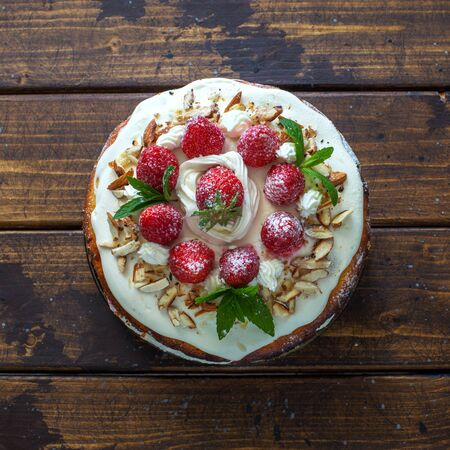 Delicious tart wih fresh strawberries and whipped cream on natural wooden background. Flat lay.