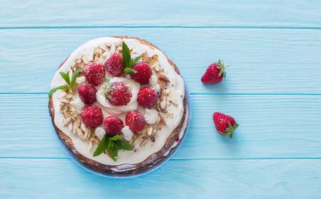 Delicious tart wih fresh strawberries and whipped cream on blue wooden background. Flat lay. Copy space