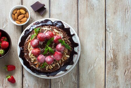 Delicious tart with strawberries, almond flakes, chocolate topping  and whipped cream close up on a natural wooden background. Flat lay. Copy space