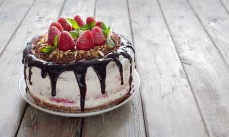 Delicious tart with strawberries, almond flakes, chocolate topping  and whipped cream close up on a natural wooden background close up