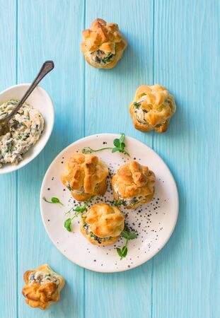Profiteroles stuffed with cream cheese, onions  and mushrooms on blue woodan background.Flat lay Banque d'images