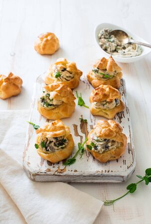 Profiteroles stuffed with cream cheese and mushrooms on white wooden background. Flat lay
