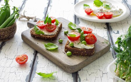 Open sandwiches with cream cheese,cherry tomatoes, green peas and basil close up. Selective focus
