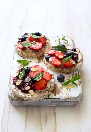 Open sandwiches with cream cheese, strawberries, blueberries, jam and almond flakes on the cutting board close up