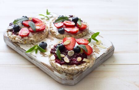 Open sandwiches with cream cheese, strawberries, blueberries, jam and almond flakes on the cutting board close up. Flat lay. Copy space