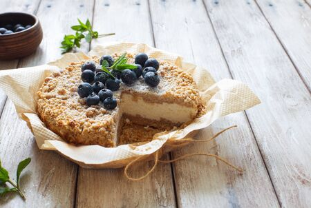 Grated rustic pie with ricotta on natural wooden background close up