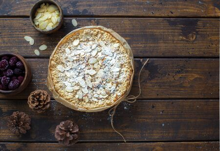 Grated rustic pie with ricotta, berries and almond flakes on dark wooden background. Flat lay