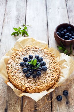 Grated rustic pie with ricotta, berries and almond flakes on natural wooden background