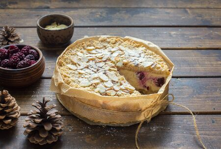 Grated rustic pie with ricotta, berries and almond flakes on natural wooden background close up