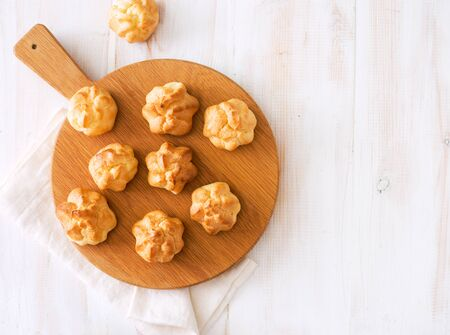 Baked homemade profiteroles on wooden cutting board. Flat lay. Copy space