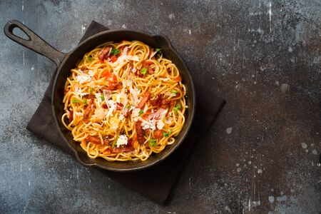 Italian pasta with roasted sausages, tomato sauce and parmesan cheese in a skillet o dark grunge background. Flat lay. Copy space
