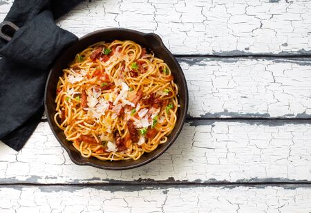 Italian pasta with roasted sausages, tomato sauce and partmesan cheese in a skillet
