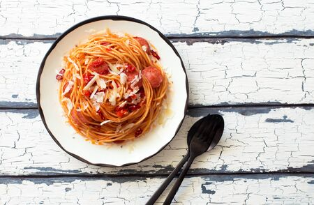 Italian pasta with sausage, tomato sauce and parmesan cheese on white plate on white wooden backgrpund. Flat lay. Copy space