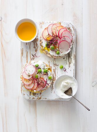 Two open sandwiches with radish, green peas, soft cheese and microgreens on white wooden background. Flat lay