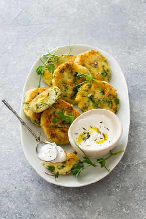 Cottage cheese pancakes with spinach served on white plate on gray stone background close up