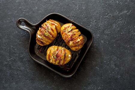 Potatoes baked with bacon, cheese and olive oil served on black plate on black stone background. Flat lay