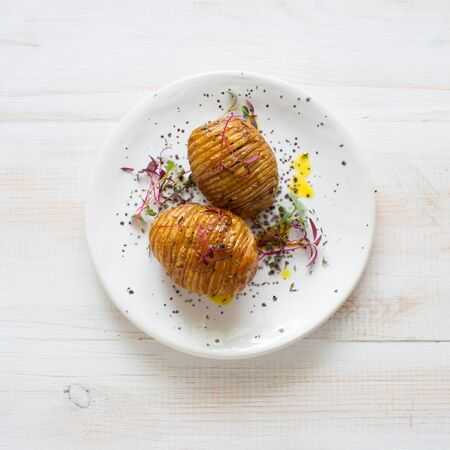 Potatoes baked with spices and olive oil served on white plate on white wooden background. Flat lay Banque d'images