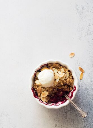 Crumble with berries, apples,almond and ball of ice steam  in white bowl close up. Flat lay. Copy space