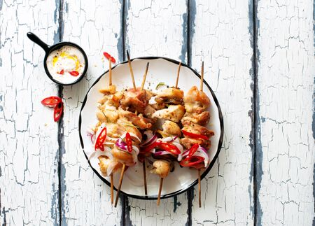 Chicken kebabs on skewers and savory cream sauce on white  plate on white  wooden table. Flat lay. Copy space. Food for a picnic