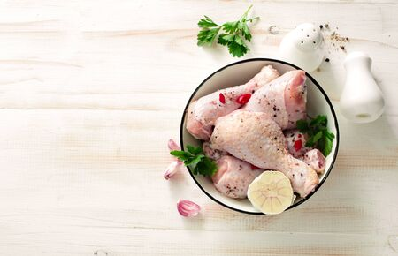 Raw chicken drumsticks with seasonings in whie bowl on white wooden table. Flat lay. Copy space