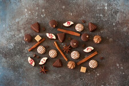 Chocolates, cinnamon, coffee beans and star anis on stone background. Top view. Copy space