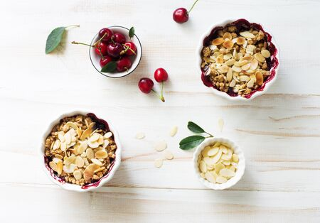 Crumble with berries, apples, and almond in white bowl on white wooden table close up. Flat lay. Copy space 免版税图像 - 150177841