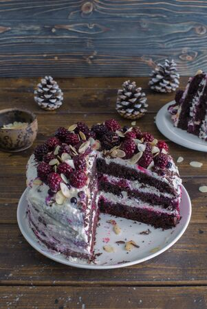 Homemade chocolate cake with brambles and almond flakes close up on dark wooden table. Selective focus 免版税图像