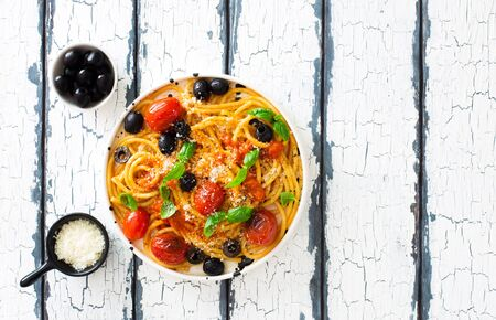 Pasta bucatini with tomato sauce, tomatoes, black olives and parmesan cheese on white grunge wooden background. Flat lay. Copy space 免版税图像