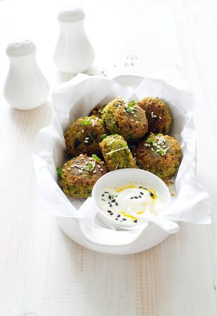 Roasted chickpeas falafel patties in white cooking tray on white wooden table close up