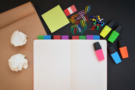 craft paper: Creative workspace with open notebook, craft paper, colorful highlighters, clips and pins on black desk