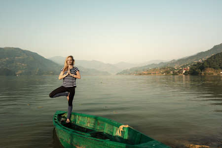Girl doing morning sports fitness exercises near  mountain lake outdoor. Yoga tour, relaxation